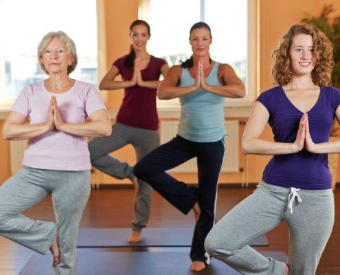 Vier Frauen machen gemeinsam Yoga in einem Sportstudio